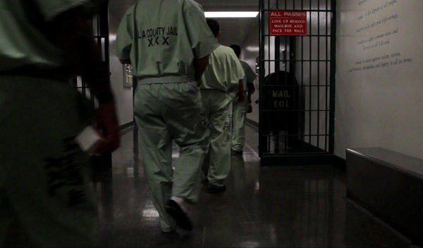 Inmates walk in a tight line to their cell blocks at the L.A. County Jail in September 2013.