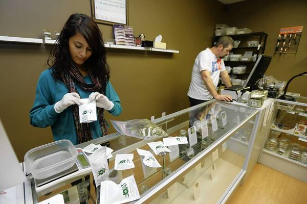 Monique Rydberg, left, packages medical marijuana as Jeff Clark awaits customers at the Joint, a medical marijuana cooperative in Seattle.