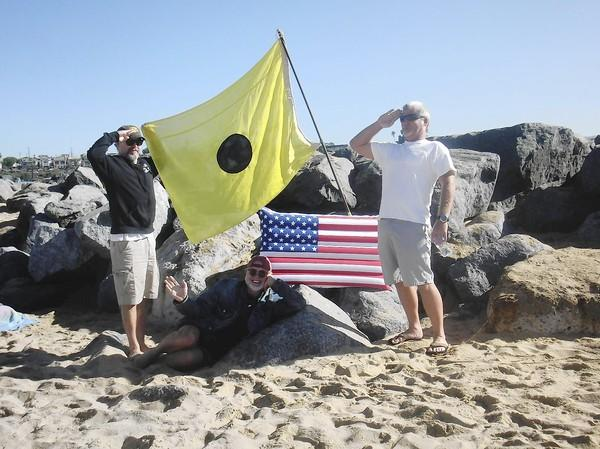 "Kevin ""Mel"" Thoman, left, with Craig Plitt, right, and Lance Jenks below the flag."