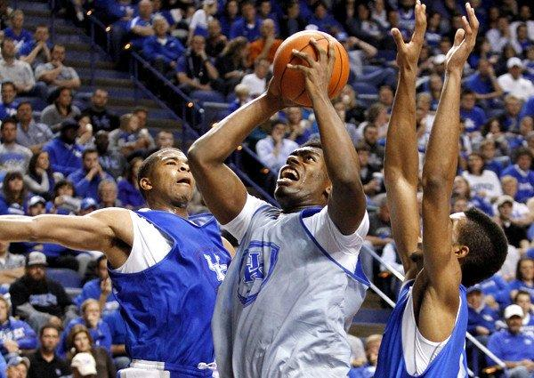 Dakari Johnson shoots between Aaron Harrison, left, and Marcus Lee during a Kentucky scrimmage on Tuesday in Lexington.