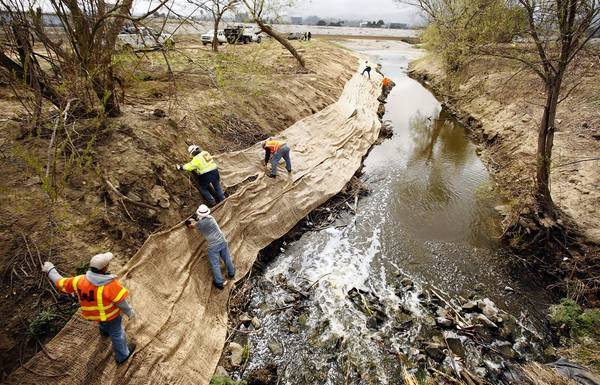 Members of the U.S. Army Corps of Engineers secure jute netting to stabilize topsoil and minimize bank erosion along Haskell Creek in February 2013 after bulldozing the area two months earlier.
