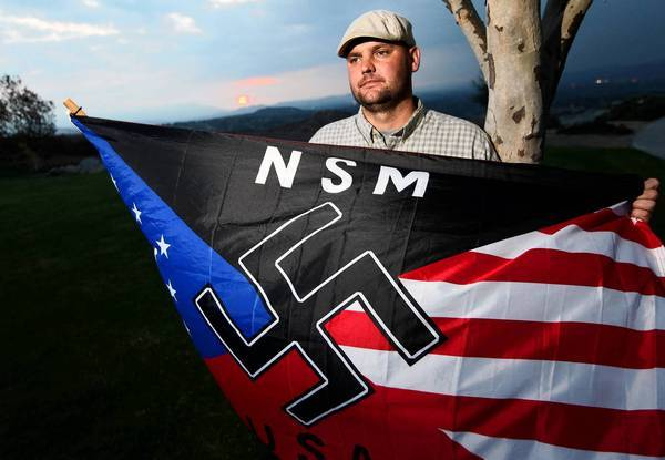 Jeffrey Hall, a leader of the neo-Nazi National Socialist Movement, was shot in the head as he slept on the couch.