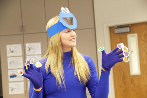 Whitney Kemink, dressed as Cookie Monster, gives a presentation on Sesame Street during social studies methods class at Northern State University on Thursday. The assignment has students doing projects on topics related to the 1960s and early 1970s. Sesame Street first aired in 1969.