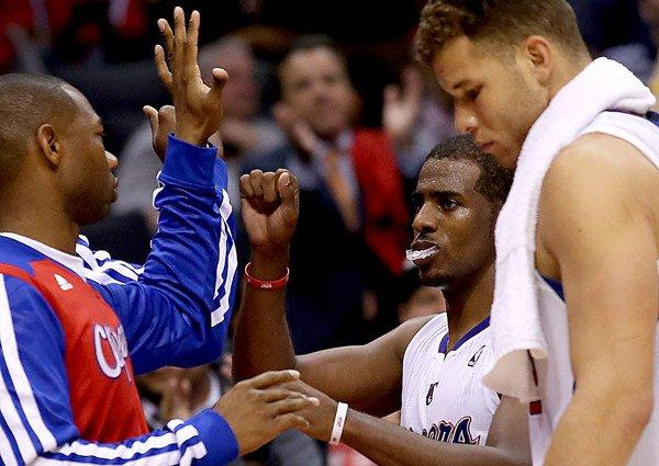 Clippers point guard Chris Paul, center, is congratulated by teammate Willie Green as he leaves the game against the Warriors in the fourth quarter with a victory secured.