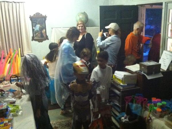 Nelson Farley, in orange, lets a group of children and parents into his home on Halloween night to pick out a toy. Farley, 79, has been giving children toys during the holiday for more than 40 years. Because the event has grown so much, Hilton Presbyterian Church will take it over next year.