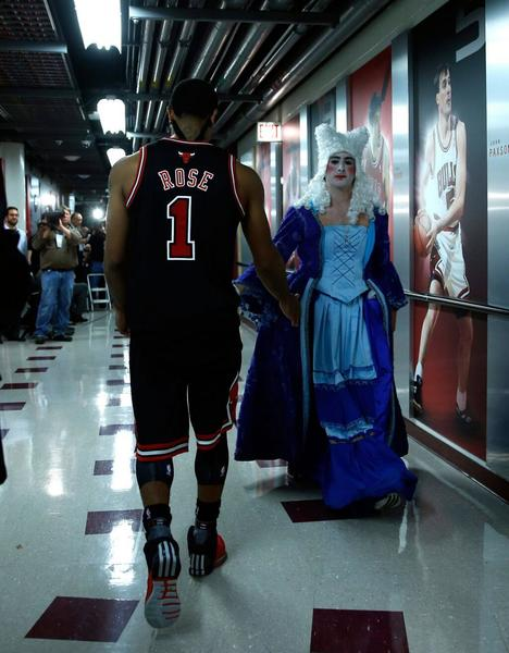 Derrick Rose is congratulated by costume-wearing Mikey Gendell after the Bulls game on Halloween night.