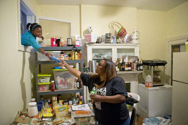 Jennifer Donald, whose family receives money from the Supplemental Nutrition Assistance Program also known as food stamps, takes a box of taco seasoning from her daughter Jayla, 10, in Philadelphia. Families already buffeted by difficult economic times saw their food stamps benefits drop Friday.