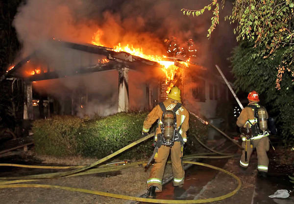 Burbank firefighters battle a house fire at 910 Evergreen St., which left a 69-year-old woman dead and two others injured.