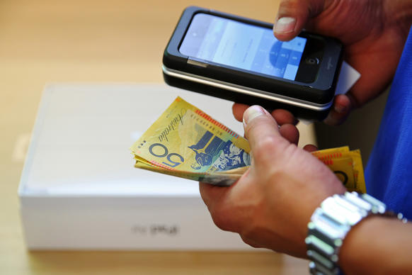 An Apple Inc. employee holds Australian dollar banknotes as a new iPad Air is purchased at the company's George Street store in Sydney, Australia, on Friday.
