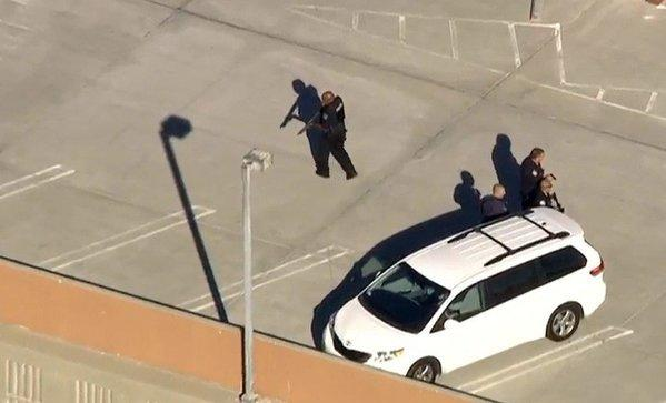 Police officials comb a LAX parking garage Friday after reports of a shooting.