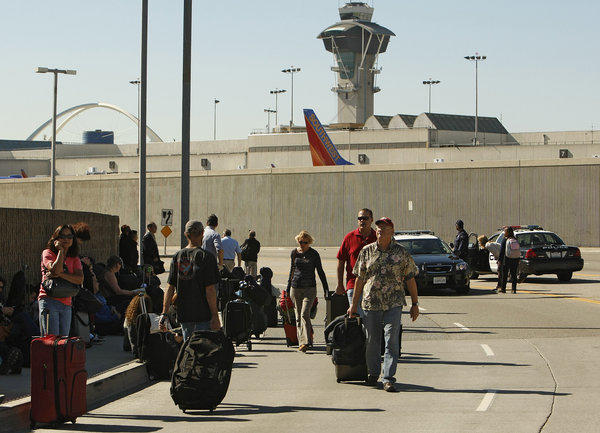 Passengers evacuated from LAX terminals walk with their luggage after a gunman opened fire inside Terminal 3.