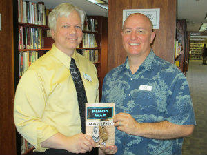 "James J. Frey (R) donates a copy of his new novel ""Kimo's War"" to the Williamsburg Regional Library. Accepting the donation is Adult Services Librarian Neil Hollands."