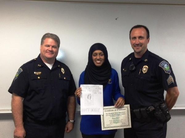 Police Chief Marc Montminy, left, and Sgt. Rob Stanford pose with poster contest winner Faryal Taseer.