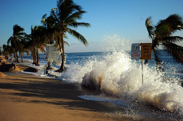 Waves crash over the seawall near a lifeguard tower on A1A in Fort Lauderdale as Hurricane Sandy brushes by South Florida