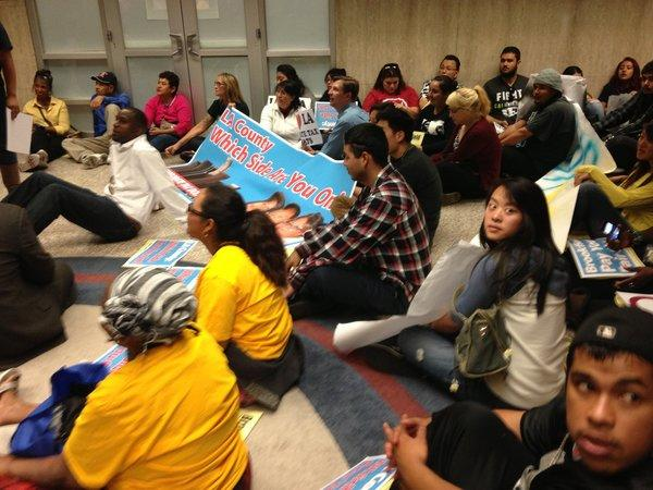 Protesters stage a sit-in outside the office of Los Angeles County Chief Executive William T Fujioka on Nov. 1, calling on the county to scrutinize the property tax assessments of Brookfield Office Properties, a major commercial property owner.