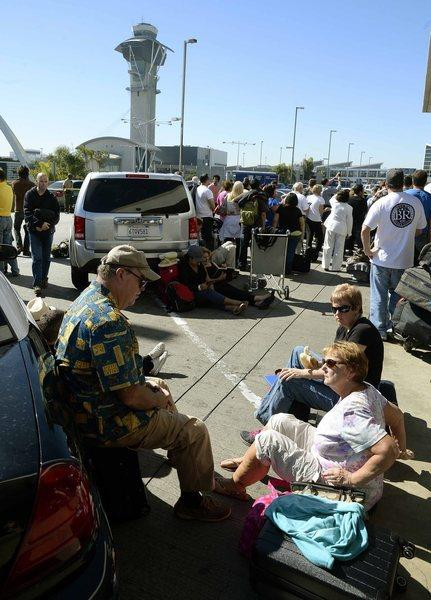 Passengers wait outside LAX Terminal 1 after thousands were evacuated after a shooting in Terminal 3.