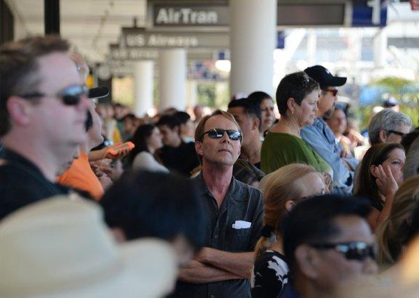 Delayed passengers and others wait behind police lines after a shooting at Los Angeles International Airport. Hotels near the airport are selling out.