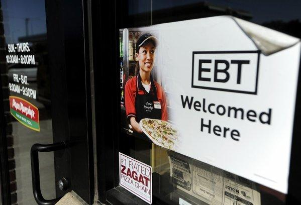 On Friday, the federal government rolled back Food Stamp benefits for all 48 million people who receive them. Above, a sign notifies customers that EBT can be used at a store in Sioux Falls, S.D.
