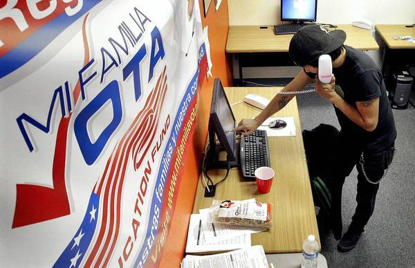 A worker for Mi Familia Vota in Phoenix works to get out the vote in 2012. Opponents of a new state election law – which they say is intended to discourage voting by minorities – are challenging it with a ballot measure.