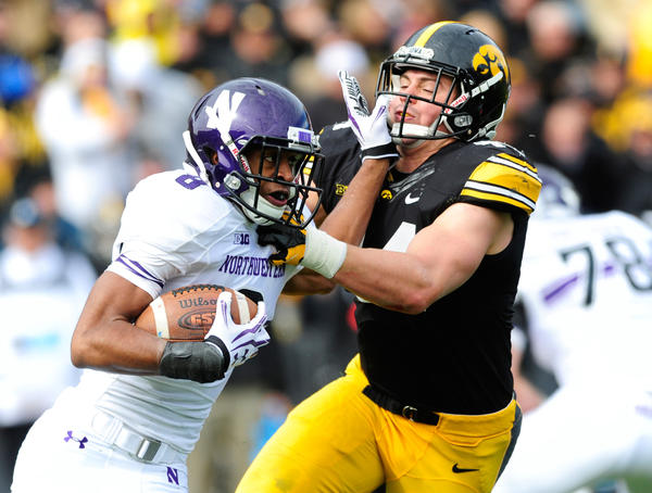 Northwestern running back Stephen Buckley fends off Iowa's James Morris in the second quarter at Kinnick Stadium.