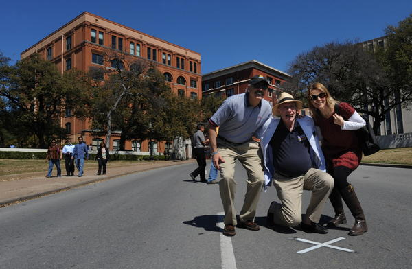 Tourists pose for photos on March 13, 2010 at the spot in front of the former Texas School Book Depository Building (L) in Dealey Plaza, where the 1963 assasination of US President John F. Kennedy took place in Dallas.
