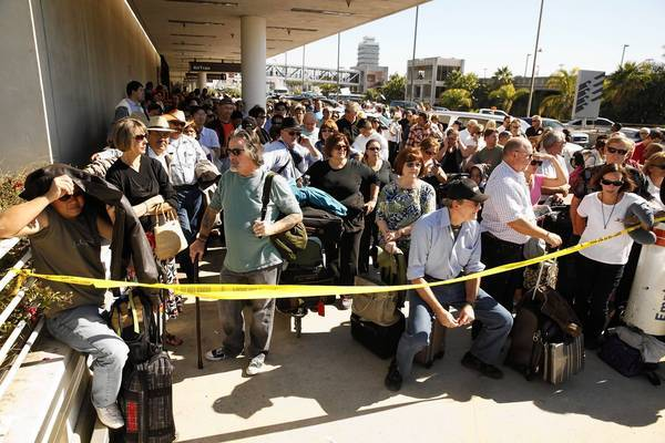 Passengers wait at Terminal 1. At least 118 flights en route to LAX were canceled or rerouted; 135 departing flights were canceled.