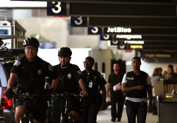 Police officers make their way through Terminal 3 at LAX, where a gunman opened fire, killing a TSA agent and wounding several others.