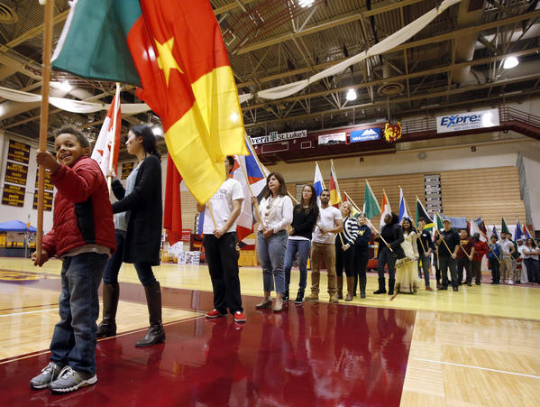 Asi Temoka, 7, waves the flag of Cameroon, as he waits his turn to take the stage during the Parade of Cultures Friday evening at the Culturefest at Wachs Arena. Students and area residents representing 35 countries and the state of South Dakota carried flags during the ceremony. American News Photo by John Davis