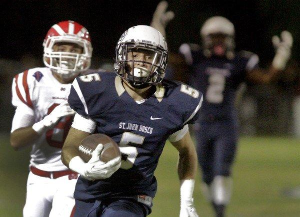 St. John Bosco running back Sean McGrew scores the first of his two touchdowns in the first half against Mater Dei on Friday night.