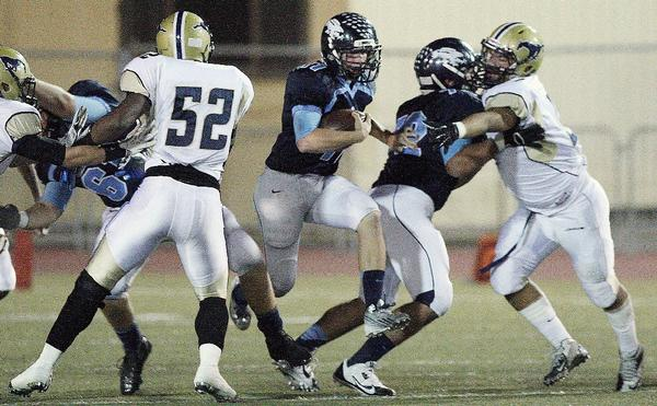 Crescenta Valley High's Kevin Hello tries to get past the Muir defense during a Pacific League game on Friday. Muir won, 39-26. (Roger Wilson/Staff Photographer)