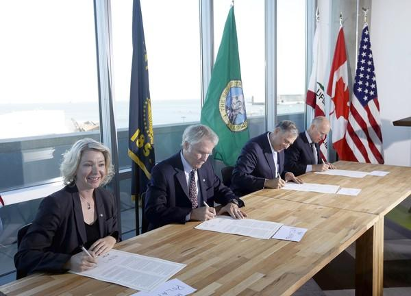 From left, Mary Polak, environment minister of British Columbia, Oregon Gov. John Kitzhaber, Washington Gov. Jay Inslee and California Gov. Jerry Brown sign an agreement to collectively combat climate change on Monday in San Francisco.
