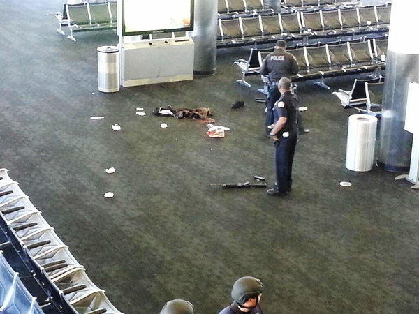 Police officers stand near an unidentified weapon in Terminal 3 of Los Angeles International Airport, where a TSA agent was killed Friday.