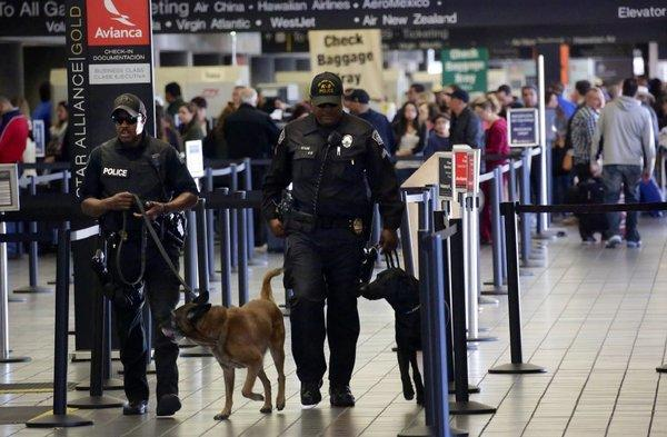 Airport police with dogs patrol Terminal 3 at LAX on Saturday, the day after a TSA officer was killed by a gunman.