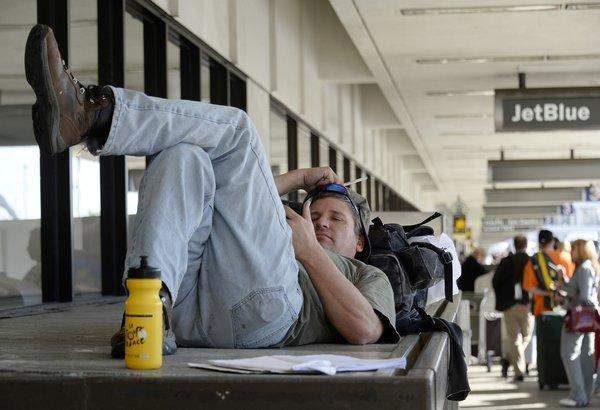 A stranded traveler, James Rusk of Fort Collins, Colo., waits for operations to get back to normal Saturday so he can take a flight out of Los Angeles International Airport.