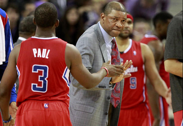 Coach Doc Rivers gives point guard Chris Paul five as the Clippers gather for a timeout in the closing seconds of a 110-101 victory over the Kings in Sacramento on Friday night.
