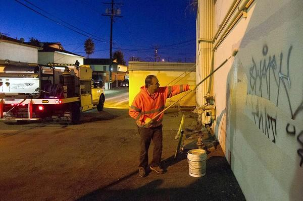 Gaetano Russo, a Costa Mesa maintenance worker, removes graffiti from a business wall in an alley on Thursday.