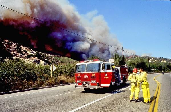 Early on in the 19993 Laguna Beach firestorm, two firefighters from Orange County Fire Station 222 survey the fire as it speeds toward the coast at the intersection at Laguna Canyon and El Toro roads. Soon it would split into two fronts and destroy more than 350 homes in Emerald Bay, Canyon Acres, Skyline, Mystic Hills and Temple Hills.