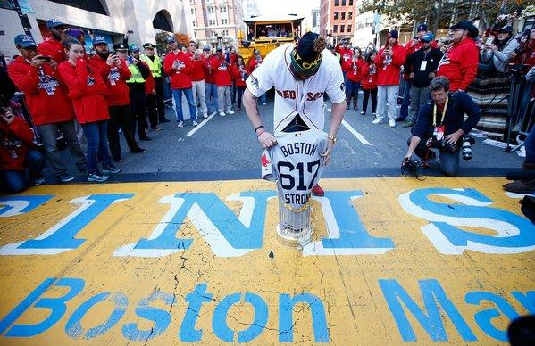 Jonny Gomes of the Boston Red Sox lays the World Series trophy and the 'Boston Strong 617' jersey onto the finish line of the Boston Marathon on Boylston Street during the World Series victory parade.