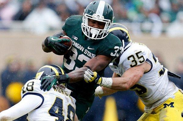 Michigan's Desmond Morgan (48) and Joe Bolden (35) bring down Michigan State's Jeremy Langford in the second quarter Saturday at Spartan Stadium.