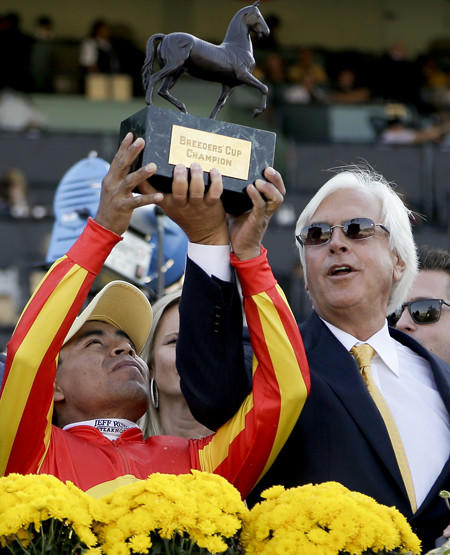 Jockey Martin Garcia and trainer Bob Baffert hold up the trophy after Secret Circle won the Breeders' Cup Sprint race on Saturday at Santa Anita Park.