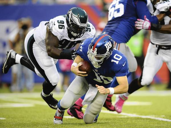 Eli Manning #10 of the New York Giants is sacked by Bennie Logan #96 of the Philadelphia Eagles in the fourth quarter at MetLife Stadium on October 6, 2013 in East Rutherford, New Jersey.