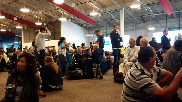 Passengers huddle together after being relocated to a secure terminal at Los Angeles International Airport on Friday. Salisbury Township resident Robby Holler was among them.