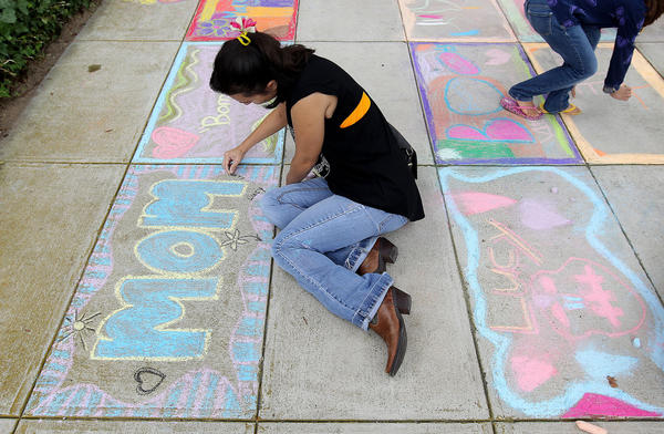 Liza Hagey draws a tribute to her mother Lusmarie at the Peninsula Fine Arts Center Saturday during an event celebrating Dia de los Muertas or the Day of the Dead. Liza lost her mother eight years ago. No Mags, No Sales, No Internet, No TV