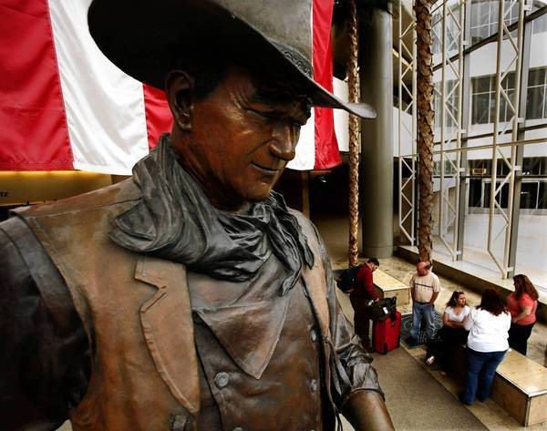 A 9-foot bronze statue of John Wayne greets passengers at John Wayne Airport in Orange County. Fewer namesakes remain in Newport Beach, the city where the screen legend spent his final years.