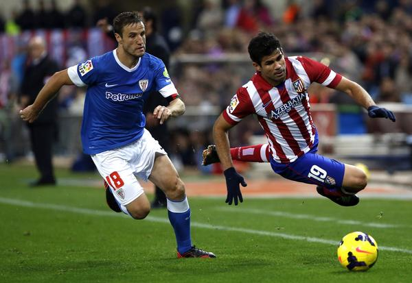 Atletico Madrid's Diego Costa (R) gets tackled by Athletic Bilbao's Carlos Gurpegui during their Spanish First Division soccer match at Vicente Calderon stadium in Madrid November 3, 2013.