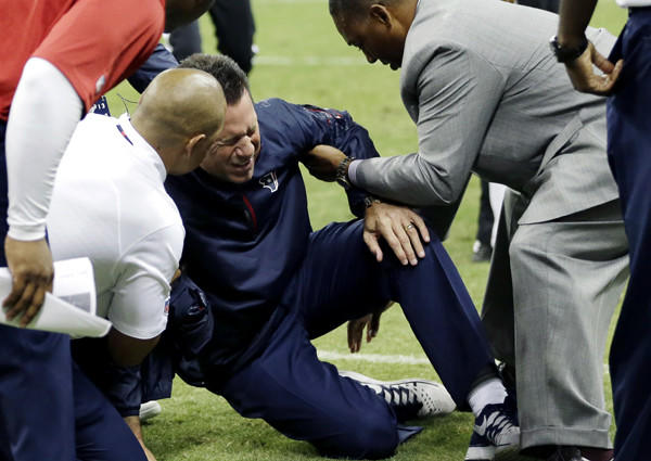 Texans Coach Gary Kubiak is given assistance by medical personnel and staff members after collapsing on the field at halftime Sunday night at Reliant Stadium in Houston.