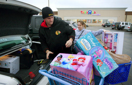 Tim Lazzara, left, and Natalie Bronge pack their car after buying toys for children in their families during Black Friday in 2012.