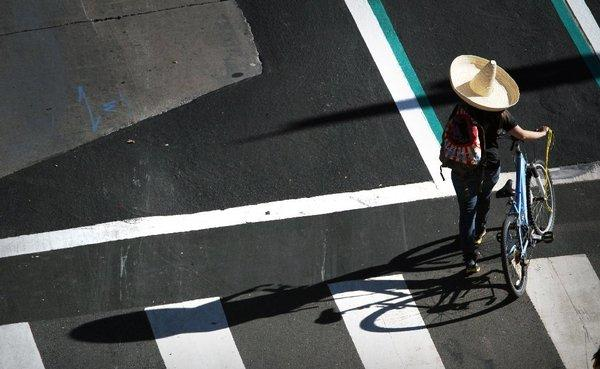 The city of Los Angeles is striping more bike lanes and increasing the visibility of crosswalks in an effort to make streets safer for pedestrians and cyclists. Above, a cyclist walks her bike in downtown L.A. during last month's CicLAvia.