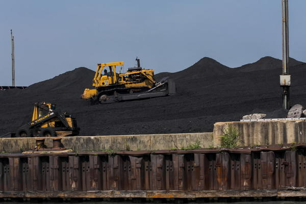 Workers handling coal and petroleum coke waste along the Calumet River in Chicago.