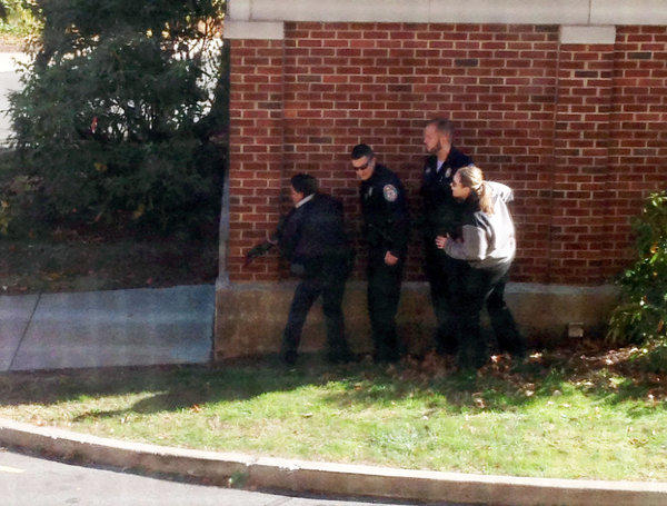 In this photo taken through a window and provided to the AP, which has been authenticated based on its contents and other AP reporting, police officers respond to a report of a suspicious person at Central Connecticut State University in New Britain, Conn.